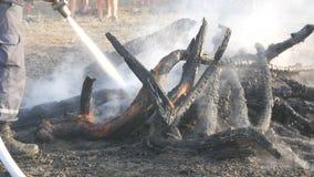 Le pompier s'éteint un feu d'un tuyau d'incendie Brûlé aux charbons, les arbres noirs fument dans la perspective des pieds clips vidéos