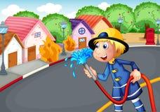 Le pompier tenant un tuyau sauvant un village sur le feu Image libre de droits