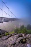 Le pont d'oscillation à hauteur de mille en brouillard, à la montagne première génération, N photographie stock