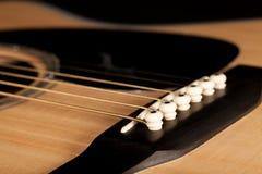 Le pont de blackwood de guitare acoustique avec la goupille cheville tenir le St de bronze Images stock