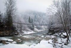 Le pont de corde à travers la rivière d'hiver de montagne avec la colline couverte par l'hiver neige-s'est recroquevillé forêt photographie stock libre de droits