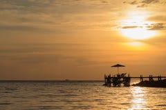 Le pont en bois au-dessus de l'océan au style de paysage de coucher du soleil type Coucher du soleil de paysage Images stock