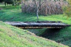 Le pont en bois fait maison court avec les poutres fortes en métal soutiennent relier deux côtés de petit canal derrière les jard images stock