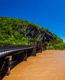 Le pont en piéton et en train à travers le fleuve Potomac inondé dans les harpistes transportent en bac, WV Photographie stock libre de droits