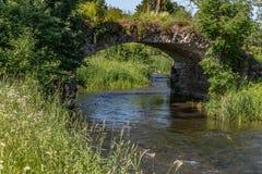 Le pont en pierre croise un courant image stock