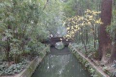 Le pont en pierre de voûte sur le fossé dans Du Fu a couvert le parc de chaume de cottage, l'adobe RVB images stock