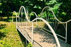 Le pont forgé blanc dans un jardin photo libre de droits