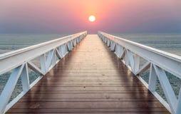 Le pont mène à la mer pendant le coucher du soleil Images libres de droits