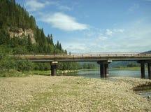 Le pont menant au-dessus de la rivière de montagne Photographie stock libre de droits
