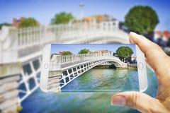 Le pont le plus célèbre à Dublin a appelé Half de pont de penny due au péage facturé le passage - le concept de Smartphone avec 3 Photos libres de droits