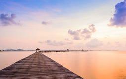 Le pont sur la plage dans le lever de soleil et la mer ondulent Images libres de droits