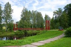 Le pont suspendu rouge par la rivière Tosna pendant l'après-midi nuageux de juillet Domaine Maryino, région de Léningrad Photo stock