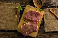 Le porc cru de vue supérieure deux morceaux ont les épices et le poivre Pétrole et sel sur la vieille table en bois Photo stock