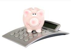 Le porc d'économie est sur la calculatrice photo libre de droits