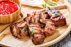 Le porc et les légumes grillés avec de la salade et le BBQ frais sauce sur la planche à découper sur le fond en bois Photos stock