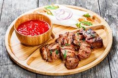 Le porc et les légumes grillés avec de la salade et le BBQ frais sauce sur la planche à découper sur le fond en bois Images stock