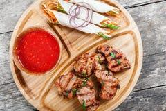Le porc et les légumes grillés avec de la salade et le BBQ frais sauce sur la planche à découper sur le fond en bois Photo stock