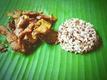 Le porc frit a alors fait frire que l'ail avec du riz de couleur sur la banane laisse Image stock
