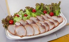 Le porc grillé tout entier a assorti avec les tomates et la laitue dans la gamelle photos libres de droits