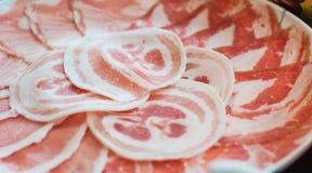 Le porc mince glisse avec de grosses lignes empilées du plat dans le restua de shabu images libres de droits