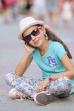 Le port élégant d'enfant de petite fille des jeans vêtx et des lunettes de soleil Images stock