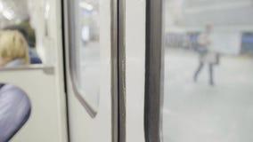 Le porte del vagon della metropolitana sono chiuse e treno con la gente che si siede sui movimenti dei sedili stock footage