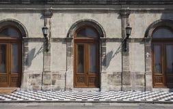 Le porte di legno del castello sulla parete lapidata e sugli scacchi gradiscono il pavimento immagine stock