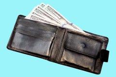 Le portefeuille en cuir noir avec des dollars sur un bleu a isolé le fond photographie stock