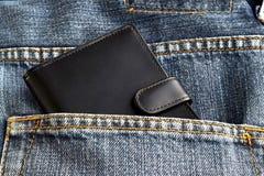 Le portefeuille noir dans des pantalons de jeans soutiennent la poche Image libre de droits