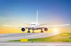 Le porteur sur le coucher du soleil de roulement sur le sol à l'aéroport, le ciel est le soleil et la voie de direction Photo stock