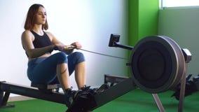 Le portraif latéral de la femme étirant son corps sur la machine à ramer dans le gymnase vert clips vidéos