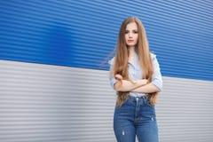 Le portrait émotif d'une femme assez blonde d'adulte avec les cheveux extra-longs magnifiques posant dehors contre le gris bleu a photos libres de droits