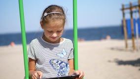 Le portrait, adolescent, fille blonde aux cheveux longs, travaille à un comprimé, sur la plage, un jour chaud d'été, contre banque de vidéos