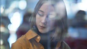 Le portrait brouillé abstrait d'une belle jeune femme dans les éclats en verre de magasin étirent des effets de foyer que la foul clips vidéos