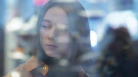 Le portrait brouillé d'une belle jeune femme dans les éclats en verre de magasin étirent des effets de foyer que la foule se dépl clips vidéos