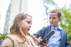 Le portrait couple les enfants, le garçon et une fille avec le téléphone extérieur les petits adultes figurent les relations malh photos libres de droits
