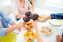 Le portrait cultivé du ` s de personnes remet les verres tintants de vin rouge Photos stock