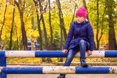Le portrait d'automne de la fille s'asseyant sur le métal siffle Photographie stock libre de droits