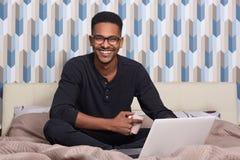 Le portrait d'intérieur du jeune homme de couleur bel s'asseyant sur le lit avec la tasse de café et les montres filment en ligne photo stock