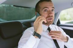 Le portrait d'intérieur d'un homme d'affaires bel invitant le téléphone intelligent redresse le lien noir et se reposer sur le si photographie stock