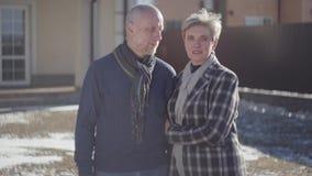 Le portrait d'un adulte la position de couples mariés par temps ensoleillé venteux frais sur le fond de leur maison famille banque de vidéos