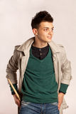 Le portrait d'un batteur avec le bâton de tambour portant un manteau et greeen la chemise dans le studio Image stock
