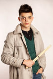 Le portrait d'un batteur avec le bâton de tambour portant un manteau et greeen la chemise dans le studio Photo libre de droits