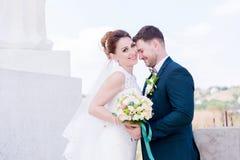 Le portrait d'un beau couple honeymooned un jour du mariage avec un bouquet à disposition dans la perspective d'un orthodoxe Photographie stock libre de droits