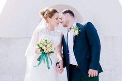 Le portrait d'un beau couple honeymooned un jour du mariage avec un bouquet à disposition dans la perspective d'un orthodoxe Image libre de droits
