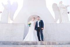 Le portrait d'un beau couple honeymooned un jour du mariage avec un bouquet à disposition dans la perspective d'un orthodoxe Photographie stock