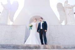 Le portrait d'un beau couple honeymooned un jour du mariage avec un bouquet à disposition dans la perspective d'un orthodoxe Photo libre de droits