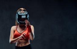 Le portrait d'un boxeur féminin de belle brune dans le soutien-gorge de sports bande ses mains D'isolement sur un fond texturisé  photo stock