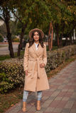 Le portrait d'un chapeau de port de fille et le manteau en automne se garent Photos stock