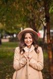Le portrait d'un chapeau de port de fille et le manteau en automne se garent Images stock